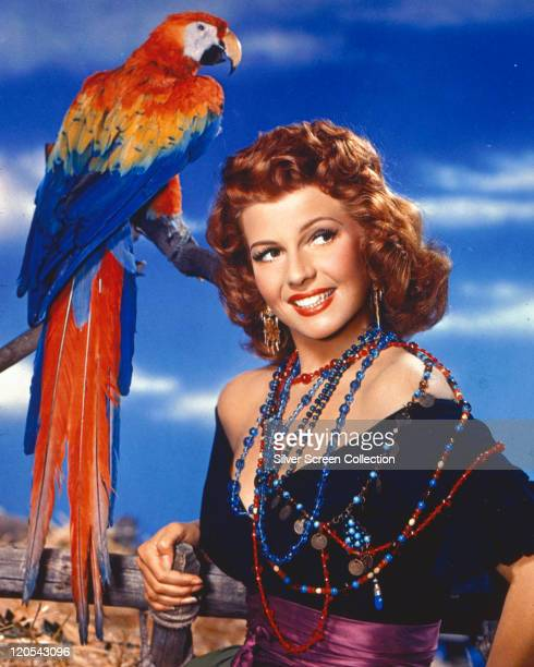 Rita Hayworth US actress and dancer wearing a number of red and blue beaded necklaces as she poses smiling beside a parrot on a perch circa 1950
