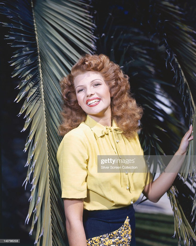 <a gi-track='captionPersonalityLinkClicked' href=/galleries/search?phrase=Rita+Hayworth&family=editorial&specificpeople=70013 ng-click='$event.stopPropagation()'>Rita Hayworth</a> (1918-1987), US actress and dancer, wearing a short-sleeve yellow blouse, posing among palm fronds, circa 1945.