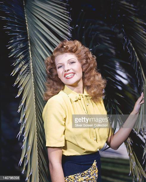 Rita Hayworth US actress and dancer wearing a shortsleeve yellow blouse posing among palm fronds circa 1945