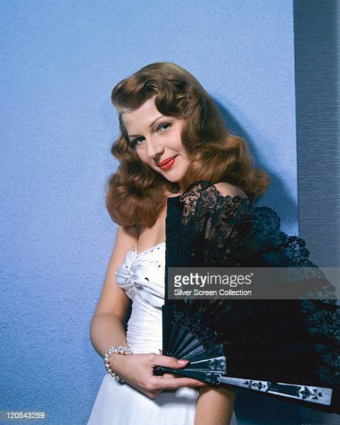 Rita Hayworth US actress and dancer wearing a white dress while posing with a black lace fan in a studio portrait circa 1945