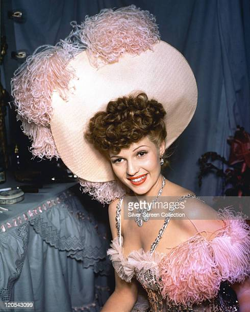 Rita Hayworth US actress and dancer wearing an outfit adorned with pink ostrich feathers on both the dress and the large pink hat circa 1955