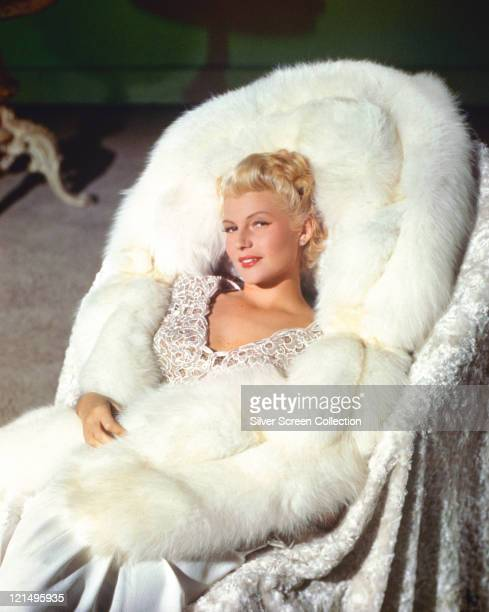 Rita Hayworth US actress and dancer with blonde hair posing on a white furlined chair in a publicity portrait issued for the film 'The Lady from...
