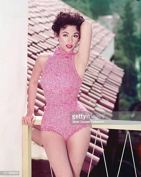 Rita Moreno Puerto Rican singer dancer and actress wearing a redandwhite halterneck swimsuit posing on a balcony overlooking a rooftop circa 1955