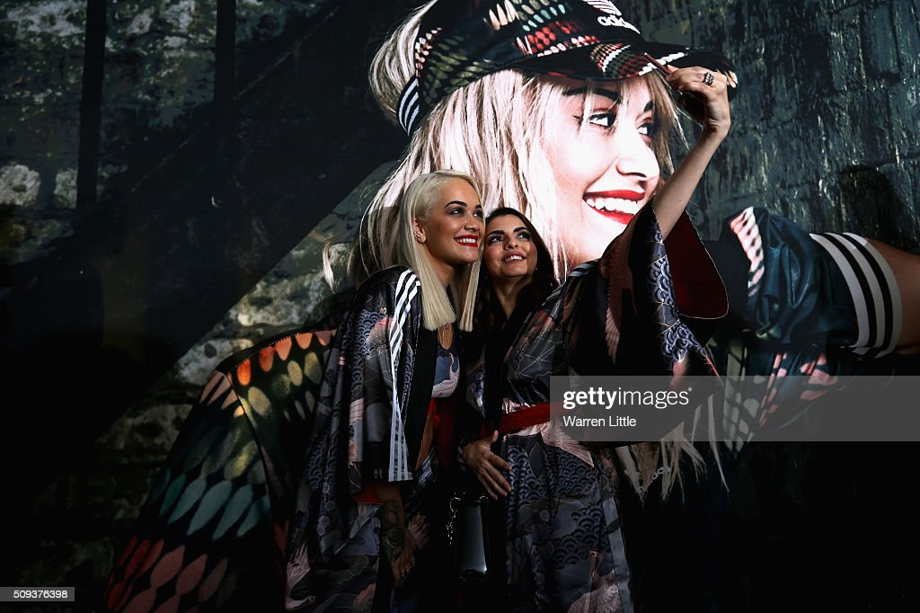 Rita Ora poses for a picture with a fan as she launches her adidas Originals Rita Ora SS16 collection at the Originals store at Dubai Mall on February 10, 2016 in Dubai, United Arab Emirates.