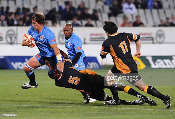 Rito Hlungwane tackles Dries van Schalkwyk during the Absa Currie Cup match between Blue Bulls and Boland at Loftus Versfeld on July 31 2009 in...