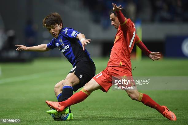 Ritsu Doan of Gamba Osaka competes for the ball against Sergio Cirio of Adelaide United during the AFC Champions League Group H match between Gamba...