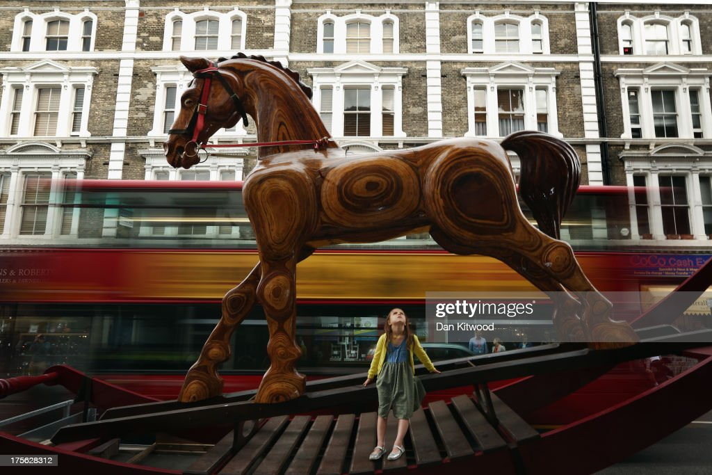 Riva Lemanski, 6, sits on an giant Rocking Horse chair outside Christie's Auction House on August 5, 2013 in London, England. The horse makes up part of the 'Out of the Ordinary' sale at Christie's Auction House, and is expected to fetch between £25,000 -£40,000 GBP when it goes on sale on September 5, 2013.
