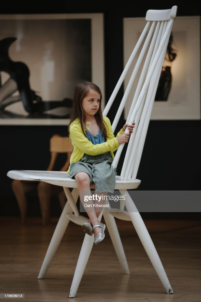 Riva Lemanski, 6, sits on an oversized 'Mademoiselle' chair at Christie's Auction House on August 5, 2013 in London, England. The chair, by Finnish designer Ilmari Tapiovaara makes up part of the 'Out of the Ordinary' sale at Christie's Auction House, and is expected to fetch between £2,000 -£3,000 GBP when it goes on sale on September 5, 2013.