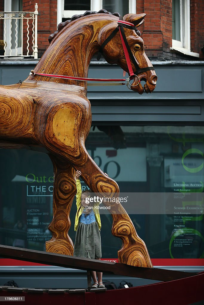 Riva Lemanski, 6, stands on an giant Rocking Horse chair outside Christie's Auction House on August 5, 2013 in London, England. The horse makes up part of the 'Out of the Ordinary' sale at Christie's Auction House, and is expected to fetch between £25,000 -£40,000 GBP when it goes on sale on September 5, 2013.