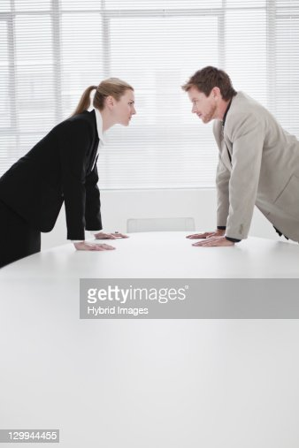 Rival business people leaning over desk