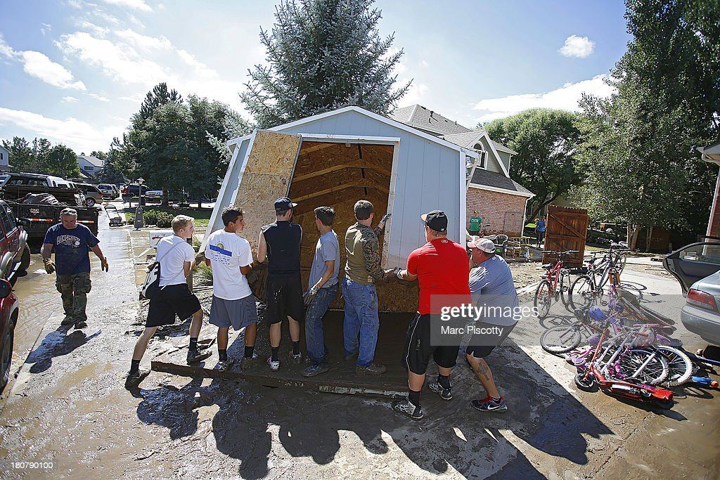 Rival members of local Longmont, Colorado high school football teams band together to help remove a shed displaced by flood waters as residents clean up in the wake of a week of heavy flooding in the Northern Colorado town on September 16, 2013 in Longmont, Colorado. More than 600 people are unaccounted for and thousands were forced to evacuate after historic flooding devastated communities in Colorado.