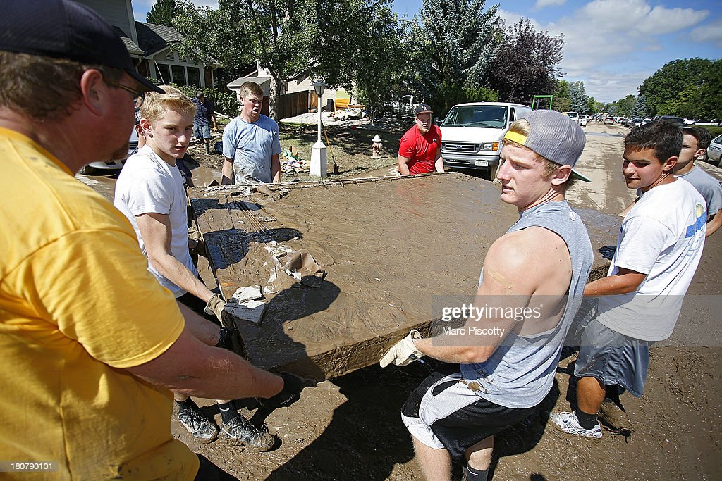 Rival members of local Longmont, Colorado high school football teams band together to help remove the floor of a shed displaced by flood waters as residents clean up in the wake of a week of heavy flooding in the Northern Colorado town on September 16, 2013 in Longmont, Colorado. More than 600 people are unaccounted for and thousands were forced to evacuate after historic flooding devastated communities in Colorado.