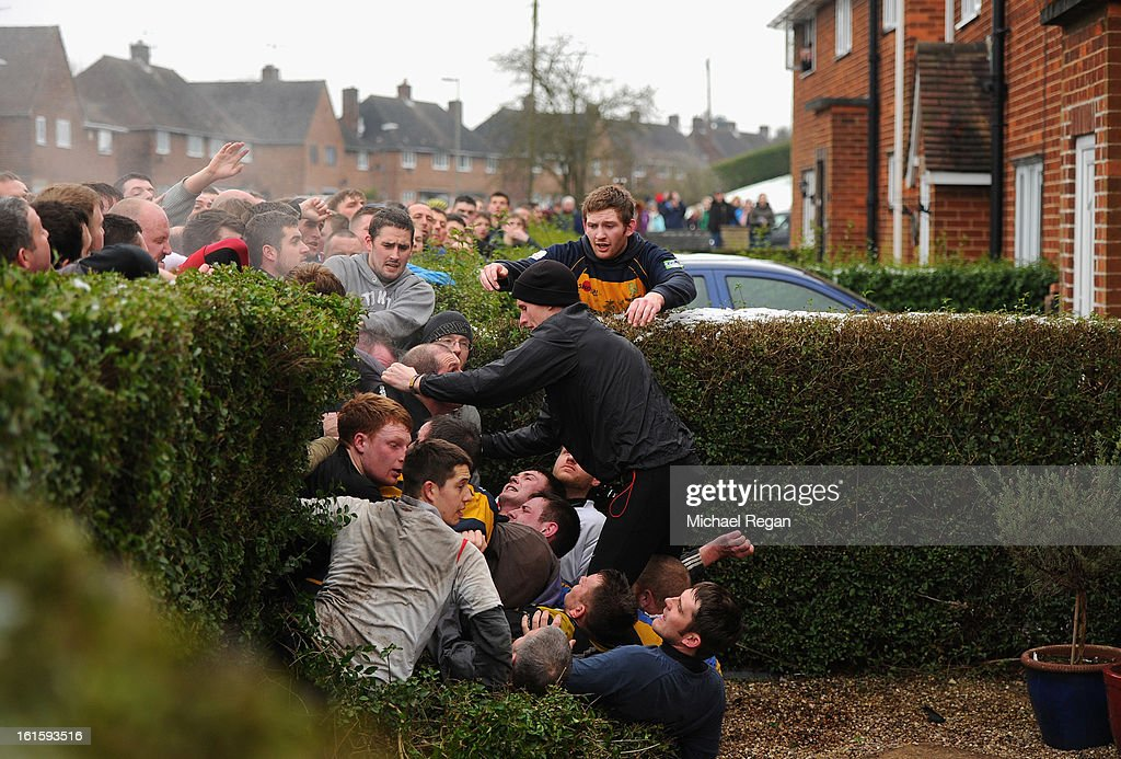 Rival teams the 'Up'ards and Down'ards' fall through a hedge into a garden as they battle for the ball in the annual Shrove Tuesday 'no rules' football match on February 12, 2013, in Ashbourne, England. First played in the 17th Century between teams from opposite ends of the Derbyshire town, hundreds of participants aim to get a ball into one of two goals that are positioned three miles apart at either end of Ashboune. The game can last until 10 PM. If a goal is scored before 6 PM, then a new ball is 'turned up' again and a new game started. If the goal is after 6 PM then the game ends for that day and continues into the next day - known as Ash Wednesday.