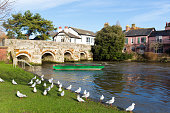 River Avon Christchurch Dorset England UK with bridge and water and a green boat near to Bournemouth and the New Forest