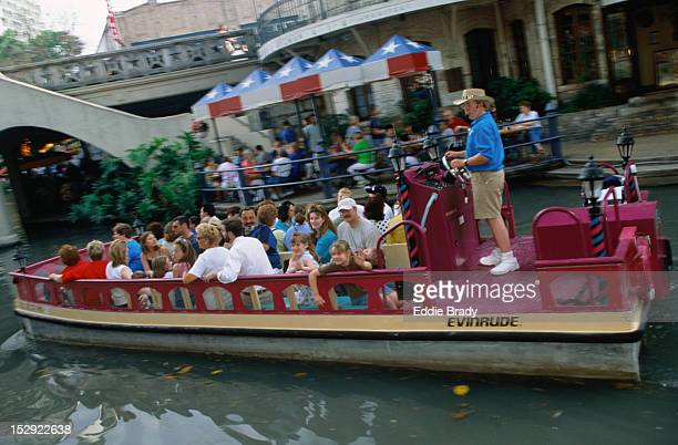 River barge with passengers tour along the Riverwalk, an area in San Antonio full of cafes, restaurants and hotels.