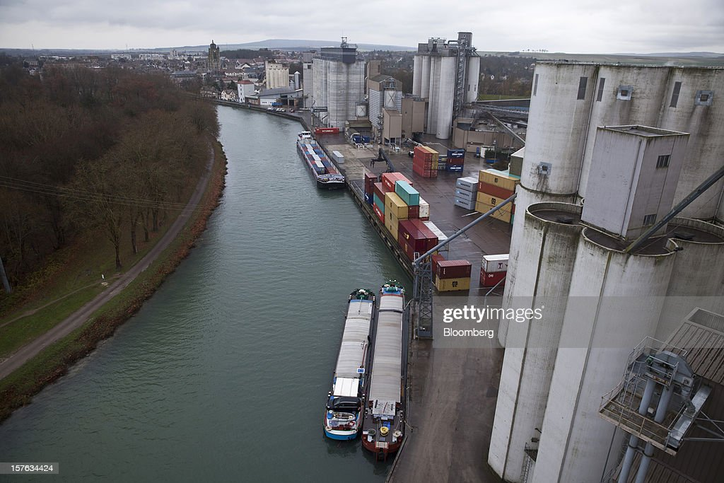 River barges, shipping containers and grain silos are seen at the dockside at the Groupe Soufflet plant in Nogent-sur-Seine, France, on Tuesday, Dec. 4, 2012. European Union corn imports may be the second-highest on record this season after drought parched crops and a surge in wheat exports curbed domestic grain supply. Photographer: Balint Porneczi/Bloomberg via Getty Images