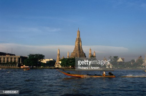 River boat on Chao Phraya (River) in front of Wat Arun.