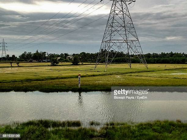 River By Electricity Pylons On Field Against Cloudy Sky