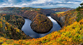 River canyon with dark water and autumn colorful forest. Horseshoe bend, Vltava river, Czech republic. Beautiful landscape with river. Maj lookout.