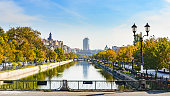 River Dambovita in Bucharest, Romania with the city skyline and colorful trees in foliage