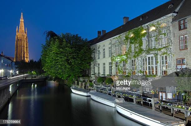 River Dijver and Our Lady chuch at dusk Brugges Flanders Belgium