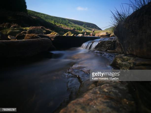 River Flowing Amidst Rocks Against Clear Sky