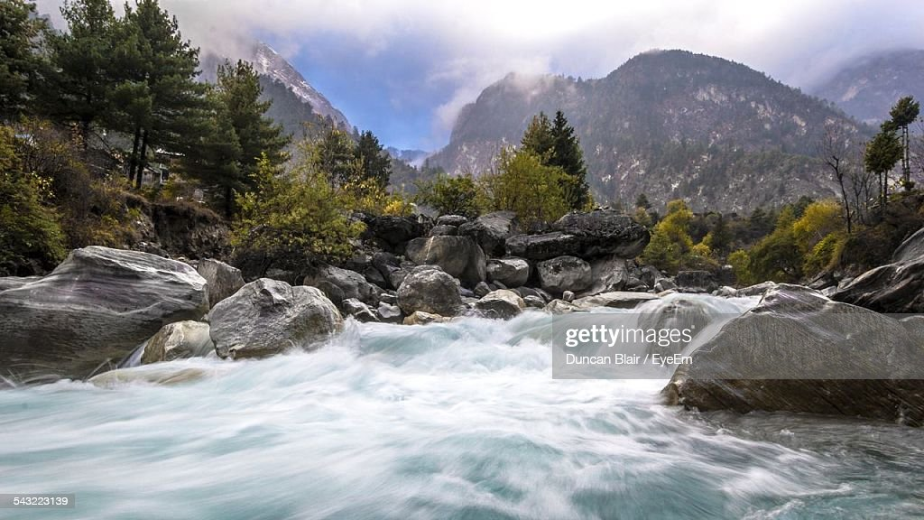 River Flowing Amidst Rocks Against Mountains