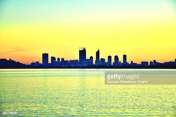 River In Front Of Cityscape Against Orange Sky During Sunset