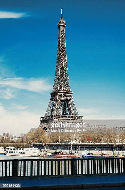 River In Front Of Eiffel Tower Against Sky In City