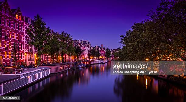 River In Illuminated City Against Sky At Night