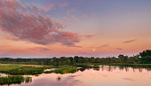 Panorama Of River Landscape In Belarus Or European Part Of Russia In Sunset Time Of Summer Evening. Moon Rising Over Water Lake Or River. Nature At Sunny Evening. Woods With Green Foliage On Riverside