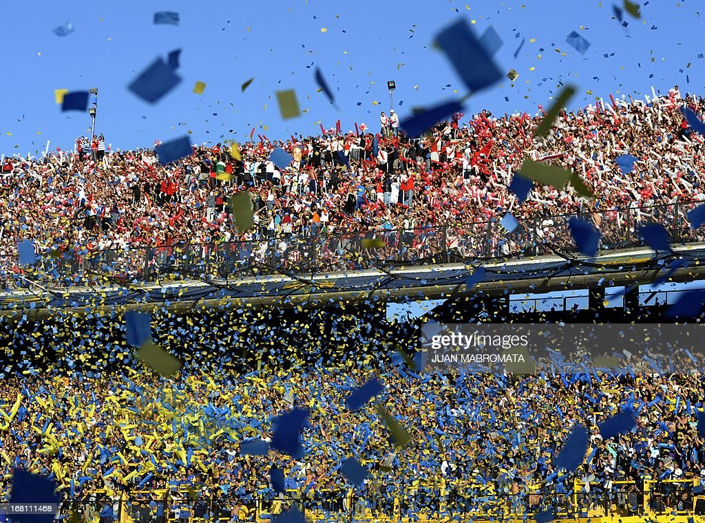 River Plate's (top) and Boca Juniors' supporters cheer for their team before the start of the Argentine first division football match at 'La Bombonera' stadium in Buenos Aires, Argentina, on May 5, 2013. AFP PHOTO / Juan Mabromata