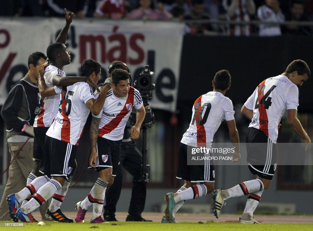 River Plate's defender Eder Alvarez Balanta (L) celebrates with teammates after scoring a goal against Quilmes during their Argentine First Division football match, at the Monumental stadium in Buenos Aires, Argentina, on April 28, 2013. AFP PHOTO / Alejandro PAGNI