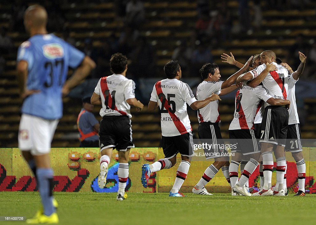 River Plate's footballers celebrate after midfielder Leonel Vangioni (hidden) scored a goal against Belgrano during their Argentine First Division football match, at Mario Alberto Kempes stadium in Cordoba, Argentina, on February 10, 2013.