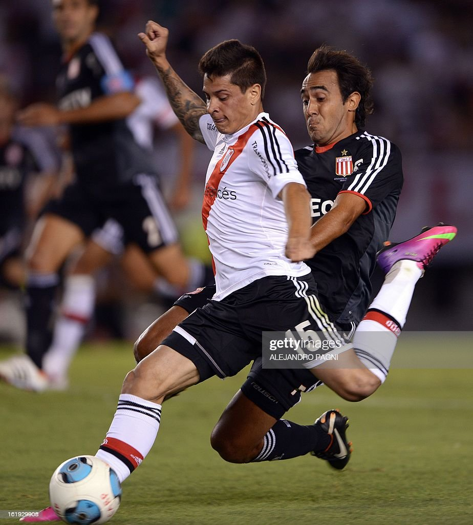 River Plate's forward Juan Manuel Iturbe (L) controls the ball past Estudiantes' midfielder Marcos Gelabert during their Argentine First Division football match, at the Monumental stadium in Buenos Aires, Argentina, on February 17, 2013. AFP PHOTO / Alejandro PAGNI