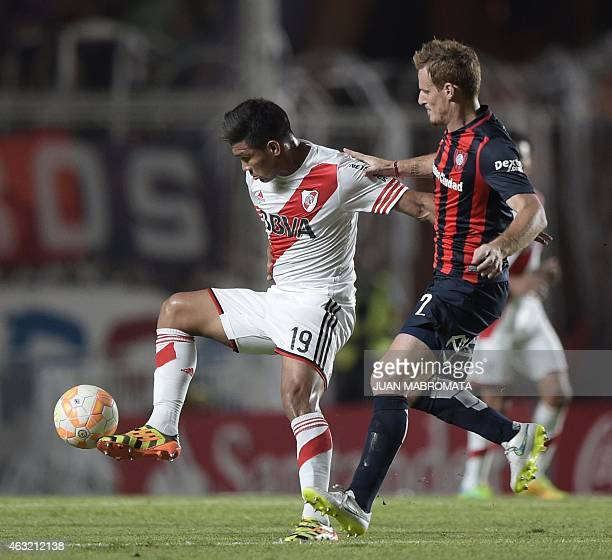 River Plate's forward Teofilo Gutierrez vies for the ball with San Lorenzo's defender Mauro Cetto during their Recopa Sudamericana 2015 second final...
