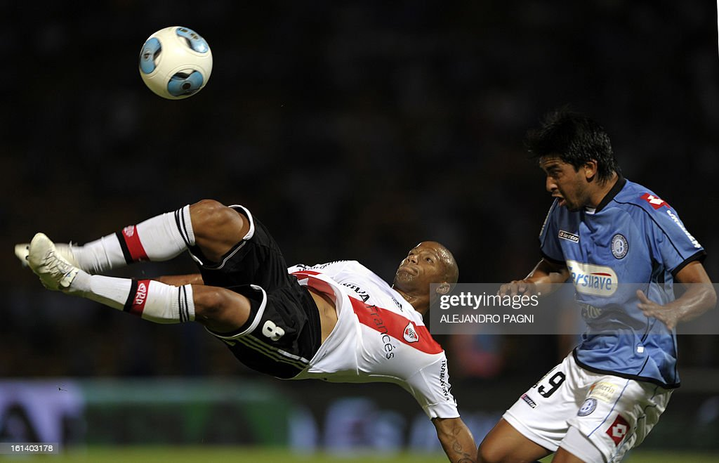 River Plate's midfielder Carlos Sanchez (L) kicks the ball next Belgrano's midfielder Jorge Velazquez during their Argentine First Division football match, at Mario Alberto Kempes stadium in Cordoba, Argentina, on February 10, 2013.