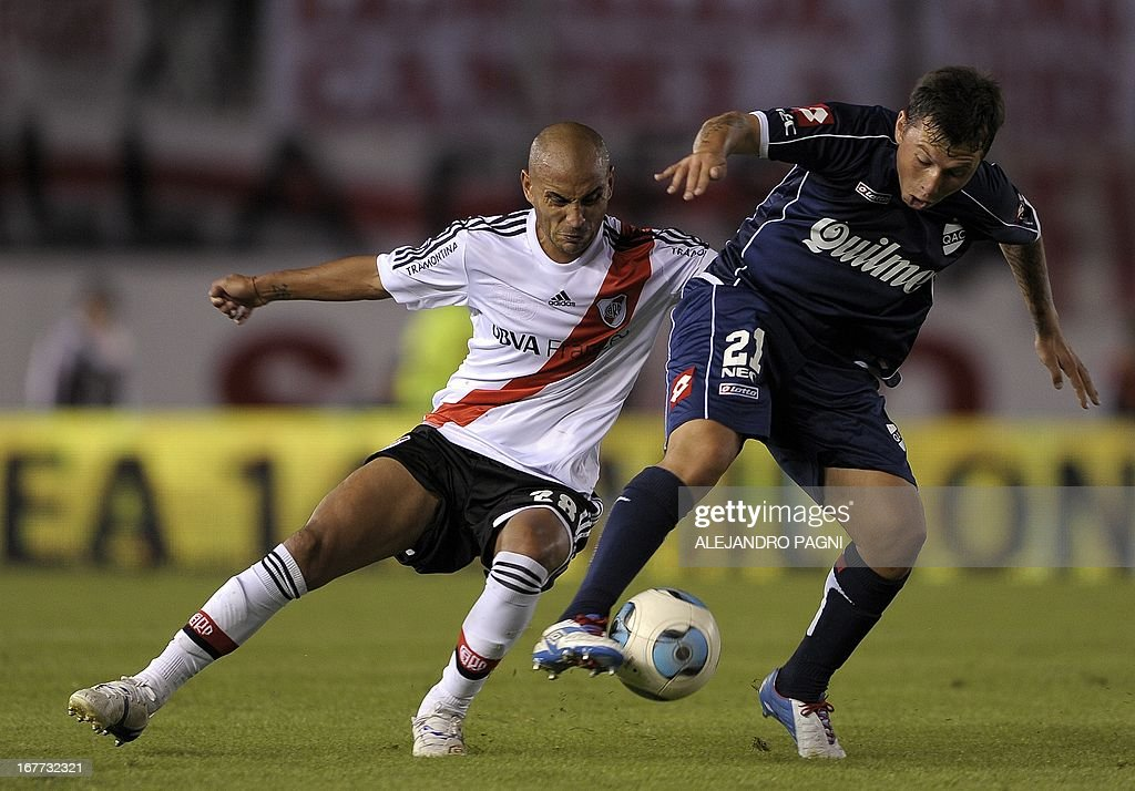 River Plate's midfielder Cristian Ledesma (L) vies for the ball with Quilmes' midfielder Gustavo Oberman during their Argentine First Division football match, at the Monumental stadium in Buenos Aires, Argentina, on April 28, 2013. AFP PHOTO / Alejandro PAGNI