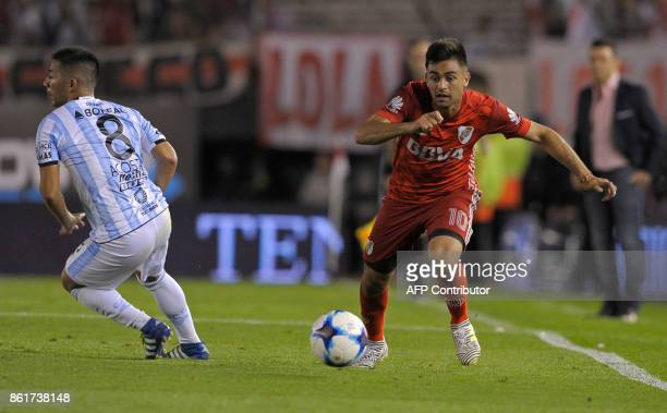 River Plate's midfielder Gonzalo Martinez controls the ball past Atletico Tucuman's midfielder Guillermo Acosta during their Argentina First Division...
