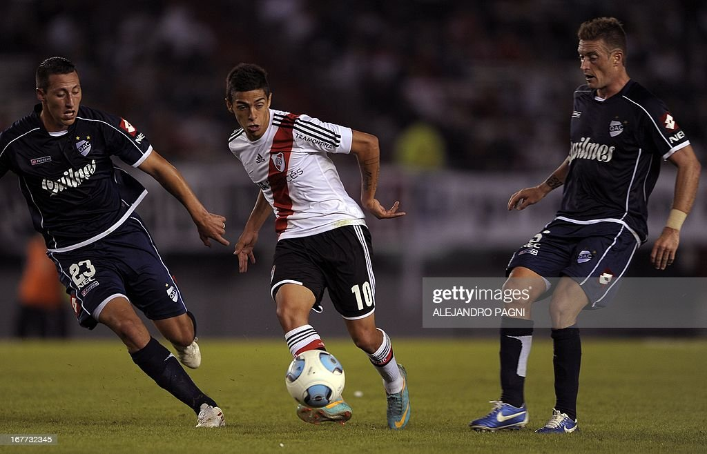 River Plate's midfielder Manuel Lanzini (C) controls the ball between Quilmes' midfielder Juan Manuel Cobo (R) and defender Cristian Lema during their Argentine First Division football match, at the Monumental stadium in Buenos Aires, Argentina, on April 28, 2013. AFP PHOTO / Alejandro PAGNI