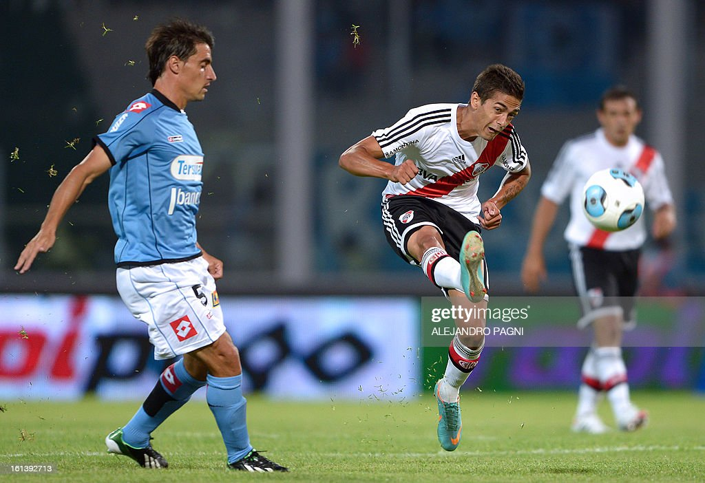 River Plate's midfielder Manuel Lanzini (C) kicks the the ball next Belgrano's midfielder Guillermo Farre during their Argentine First Division football match, at Mario Alberto Kempes stadium in Cordoba, Argentina, on February 10, 2013.