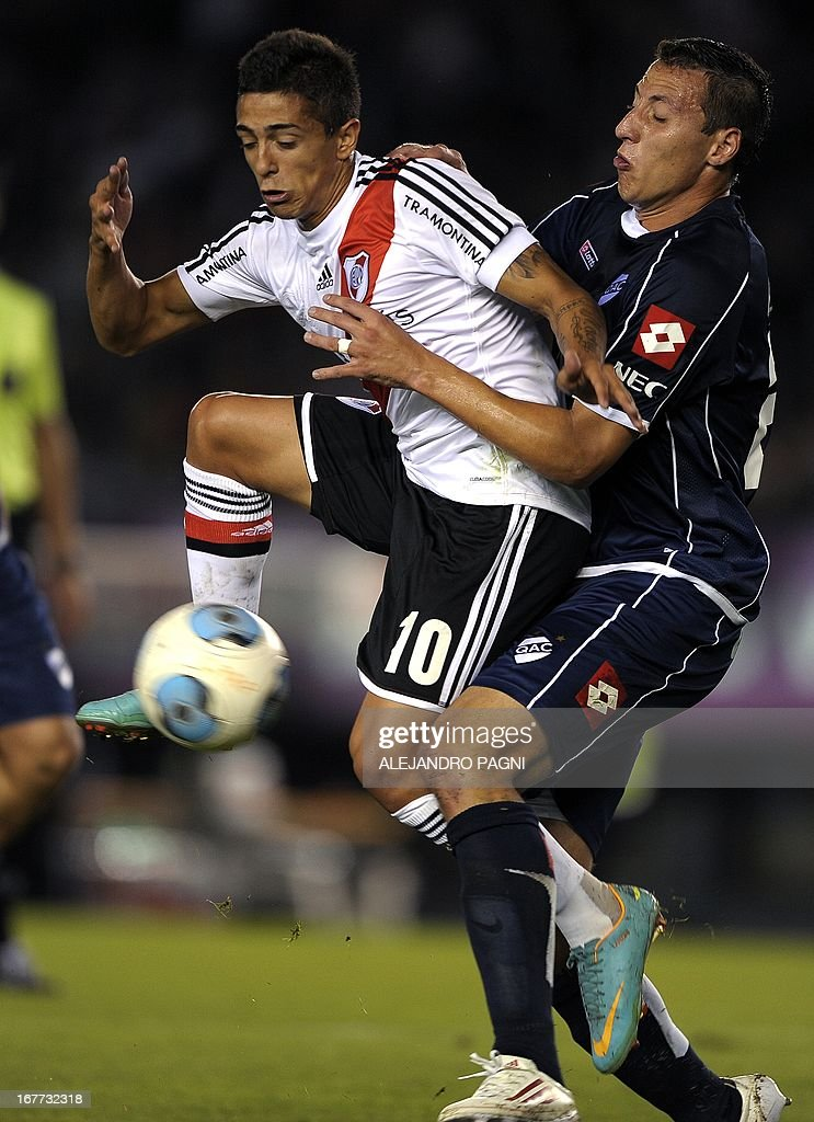 River Plate's midfielder Manuel Lanzini (L) vies for the ball with Quilmes' defender Cristian Lema during their Argentine First Division football match, at the Monumental stadium in Buenos Aires, Argentina, on April 28, 2013. AFP PHOTO / Alejandro PAGNI