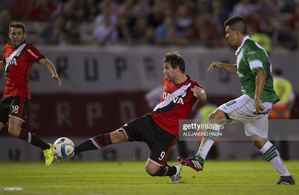 River Plate's player <a gi-track='captionPersonalityLinkClicked' href=/galleries/search?phrase=Fernando+Cavenaghi&family=editorial&specificpeople=753731 ng-click='$event.stopPropagation()'>Fernando Cavenaghi</a> (C) shoots the ball next to Banfield's defender Jorge Rodriguez (R) during their Argentina First Division football match at Antonio Liberti stadium in Buenos Aires, on April 19, 2015.