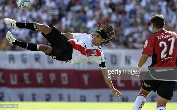River Plate's Radamel Falcao Garcia kicks the ball over Alexis Ferrero of Colon during their Argentina first division football match at Monumental...