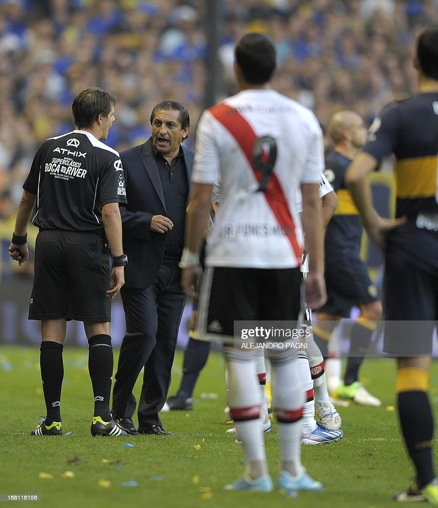 River Plate's team coach Ramon Diaz (2nd-L) argues with referee German Delfino (L) after he was dismissed during their Argentine first division football match against Boca Juniors at 'La Bombonera' stadium in Buenos Aires, Argentina, on May 5, 2013. AFP PHOTO / Alejandro PAGNI