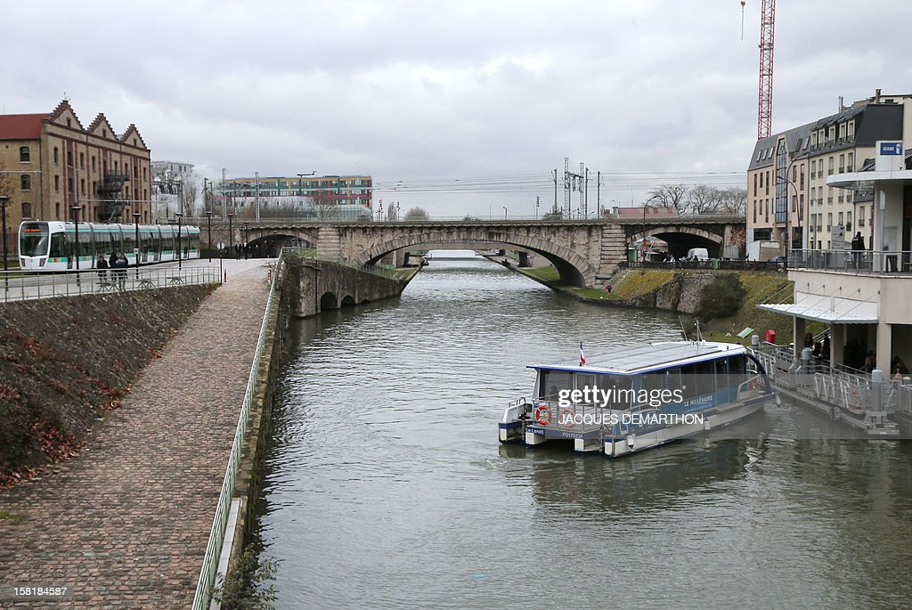 A river shuttle 'Le Millenaire' prepares to dock at the Saint-Denis canal, on December 10, 2012, in Paris. At left a T3b tramway operates on a test run.