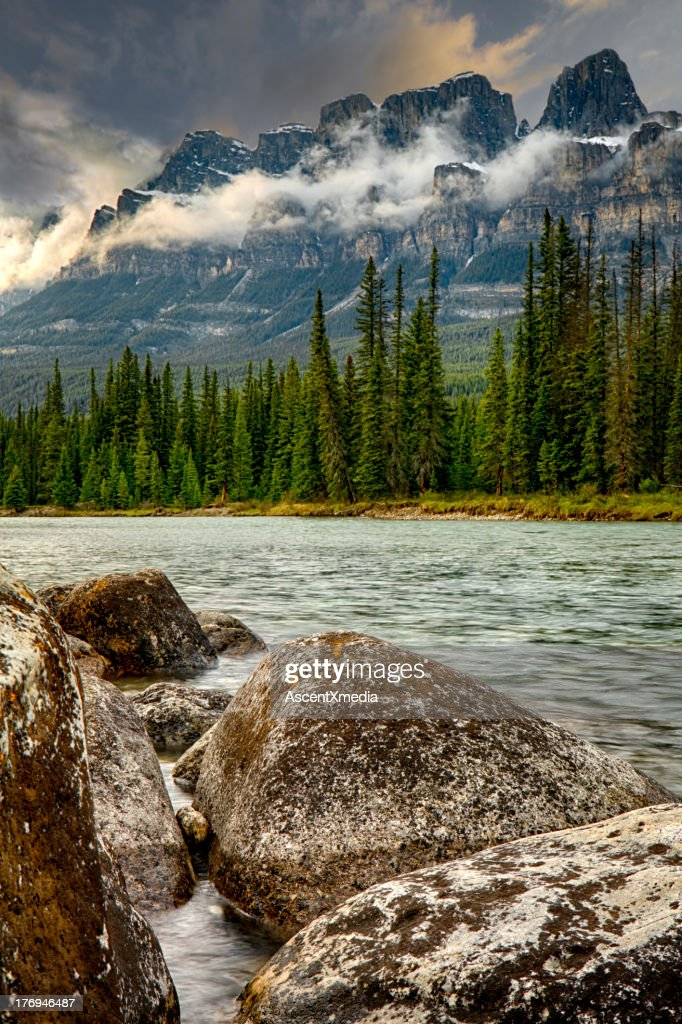 River sweeps by under mountain range, spring : Stock Photo