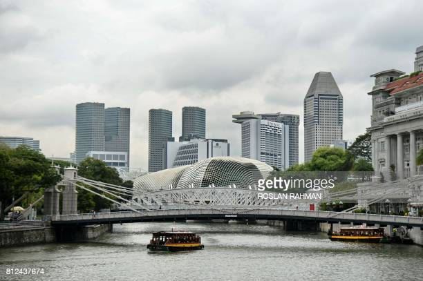 River taxi boats ply along the river next to the financial district in Singapore on July 11 2017 Singapore state investment giant Temasek Holdings'...