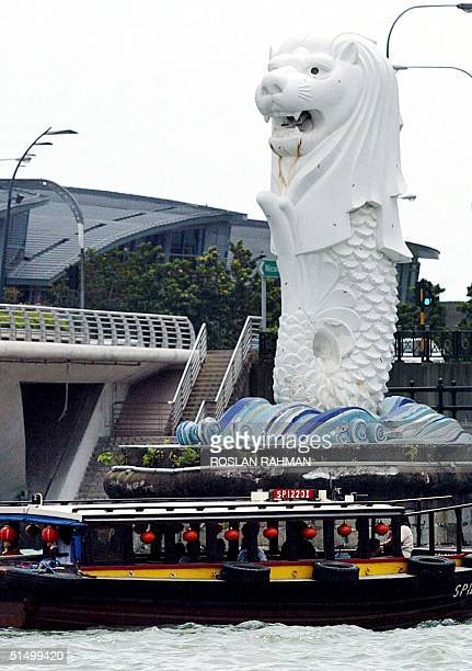 A river taxi rides past Singapore's icon the Merlion statue which sits by the Singapore River 31 January 2002 The Merlion which stands 8meter tall...