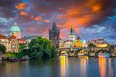 Vibrant stormy sunset sky over the River Vltava and Charles Bridge Prague Czech Republic Europe